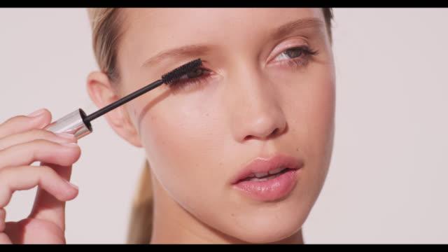 vídeos de stock, filmes e b-roll de a woman applies mascara to right eye - reluzente
