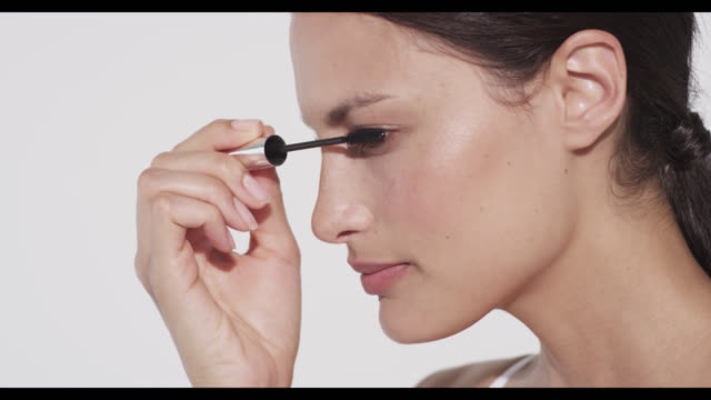 vidéos et rushes de woman applies mascara to upper lashes on left eye - mascara