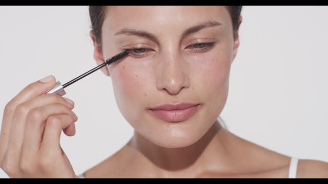 woman applies mascara to upper lashes on right eye - urbanlip stock videos & royalty-free footage