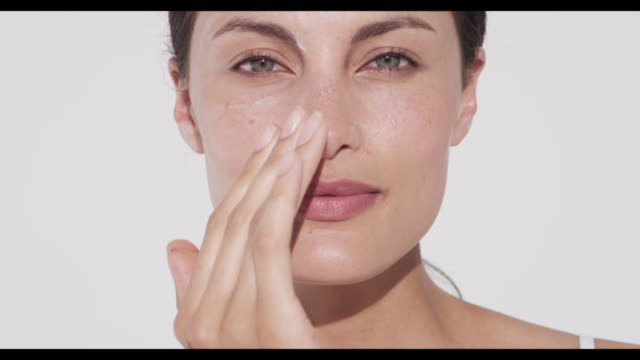 vídeos de stock e filmes b-roll de woman applies moisturiser to cheek and forehead with one hand - amimar