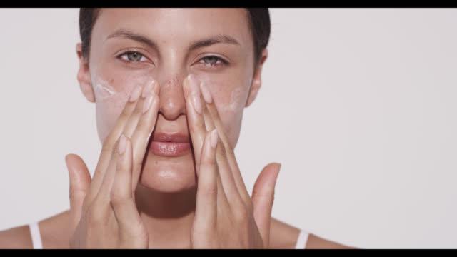 vidéos et rushes de woman applies moisturiser to cheeks with hands - appliquer