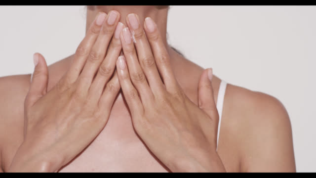 Woman applies moisturiser to neck with hands