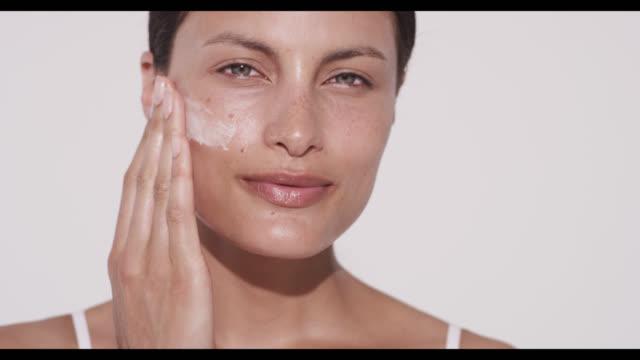 woman applies moisturiser to one cheek with hand - auftragen stock-videos und b-roll-filmmaterial
