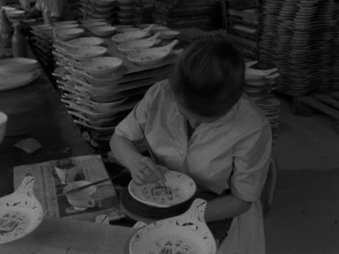 woman applies paint details to a plate at the stavanger pottery workshop. 1959. - stavanger stock videos & royalty-free footage