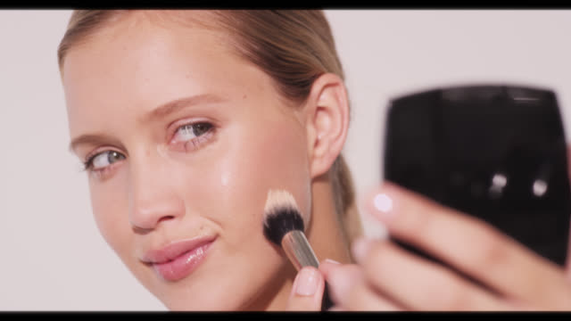 vídeos de stock, filmes e b-roll de a woman applies powder to cheek with brush and smiles - reluzente