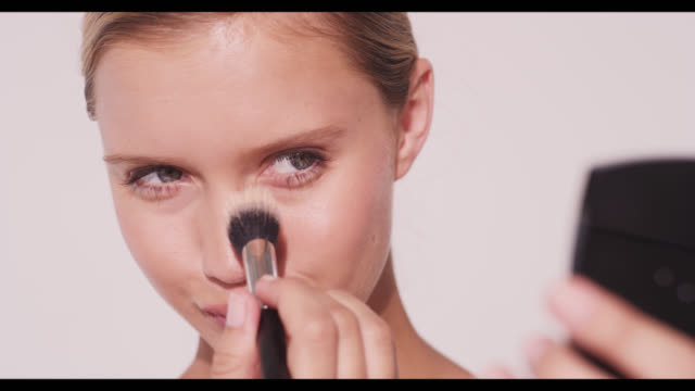 A woman applies powder to nose with brush