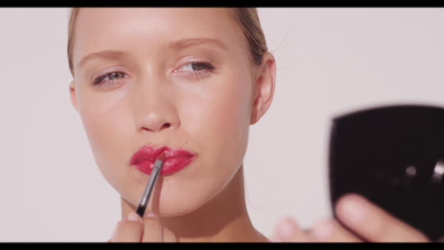 a woman applies red lip colour with lip brush - lipstick stock videos & royalty-free footage