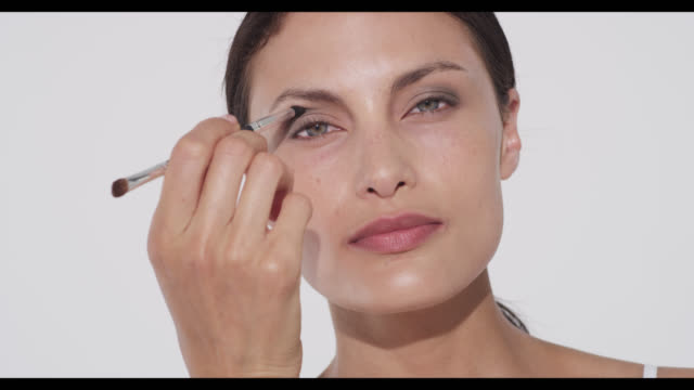 woman applies smoky grey eyeshadow to camera left eyelid with brush - make up brush stock videos & royalty-free footage