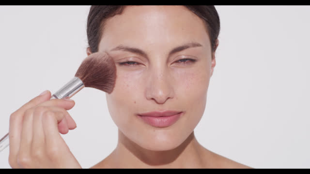 Woman applies translucent face powder to face with a brush