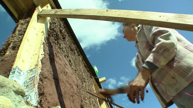 ms la woman applying adobe mud mixture to wall of straw house under construction, grass lake, michigan, usa - wall building feature stock videos & royalty-free footage