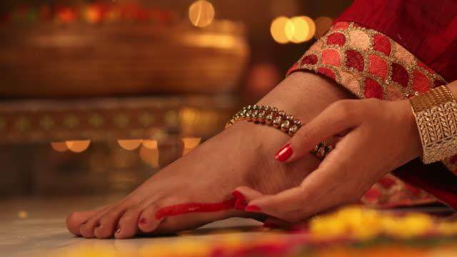 CU Woman applying alta on her foot / New Delhi, Delhi, India