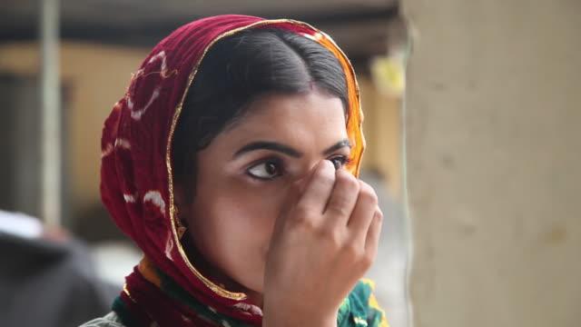 woman applying bindi on her forehead, faridabad, haryana, india  - bindi stock videos and b-roll footage