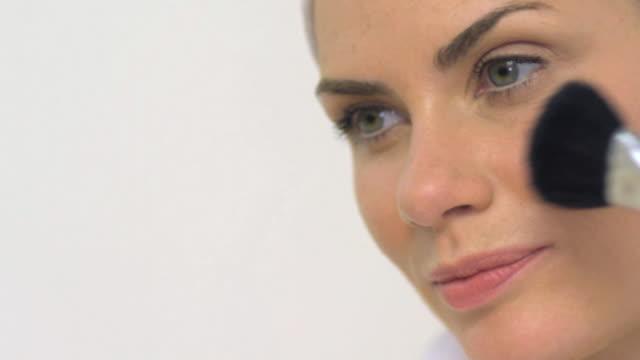 vídeos de stock, filmes e b-roll de cu pan slo mo woman applying blush / london, greater london, united kingdom  - blush