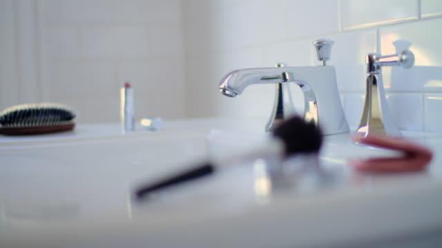woman applying blusher in bathroom mirror - フェイスブラシ点の映像素材/bロール