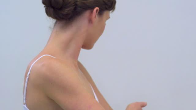 cu slo mo woman applying body lotion / london, greater london, united kingdom - chignon video stock e b–roll