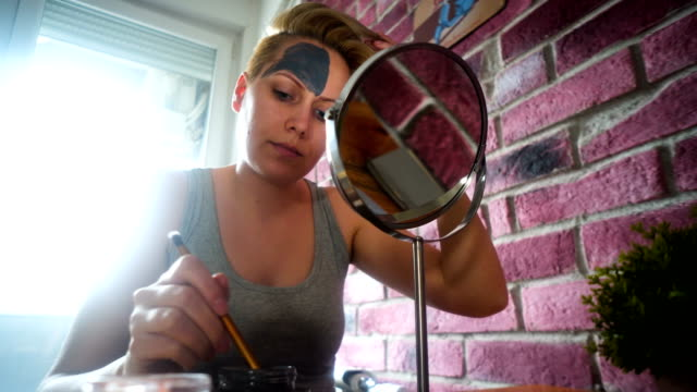 woman applying clay mask with brush at home - facial mask beauty product stock videos and b-roll footage
