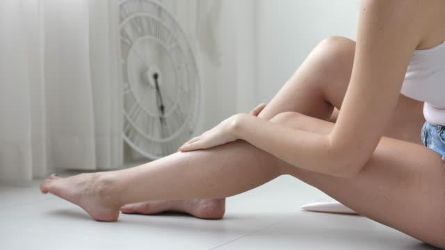彼女の長い脚にクリーム処理を施す女性がスムーズにアップ、クローズアップ - ボディケア点の映像素材/bロール