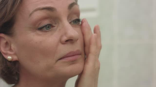 vídeos de stock e filmes b-roll de woman applying eye cream as part of her skincare routine - 50 54 anos