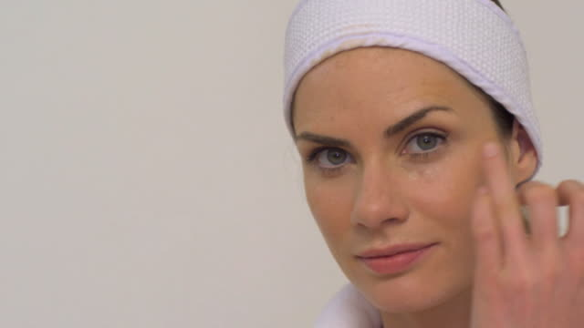 cu slo mo woman applying eye cream on face / london, greater london, united kingdom - face cream stock videos and b-roll footage