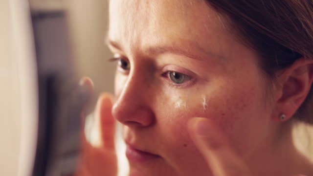 woman applying face cream. - film filmtechnik stock-videos und b-roll-filmmaterial
