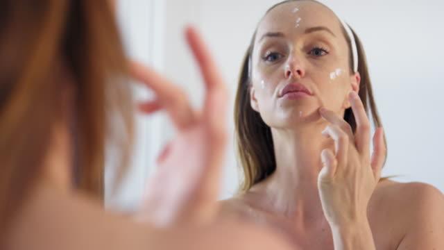 woman applying face cream - semi dress stock videos & royalty-free footage
