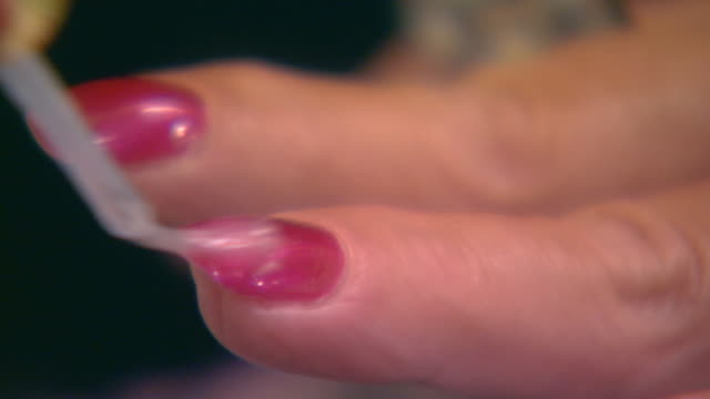 Woman applying fingernail polish, extreme close up