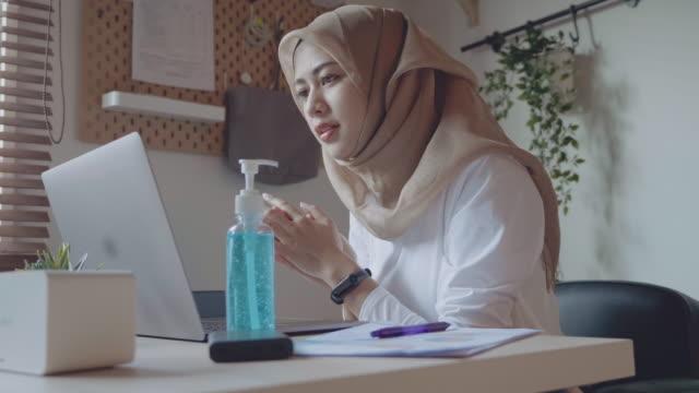 vidéos et rushes de femme appliquant le désinfectant ou le savon de main tout en travaillant de la maison. - foulard