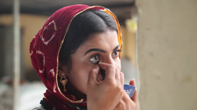 vídeos y material grabado en eventos de stock de woman applying kajal on her eyes, faridabad, haryana, india  - indian ethnicity
