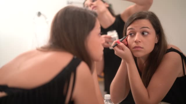 woman applying make up in bathroom mirror - blusher make up stock videos and b-roll footage