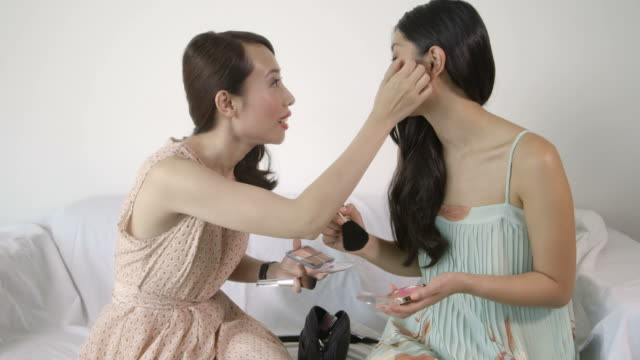 woman applying make-up and talking - サンドレス点の映像素材/bロール
