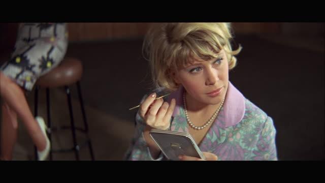 vídeos de stock e filmes b-roll de cu ha woman applying make-up holding hand mirror - olhar de lado