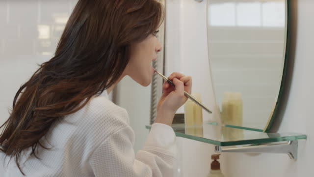 slo mo ms tu woman applying make-up in bathroom / salt lake city, utah, usa - メイクアップ点の映像素材/bロール