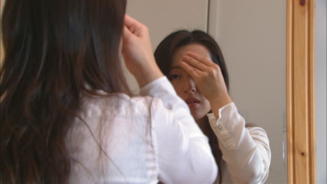 CU, Woman applying make-up in front of mirror