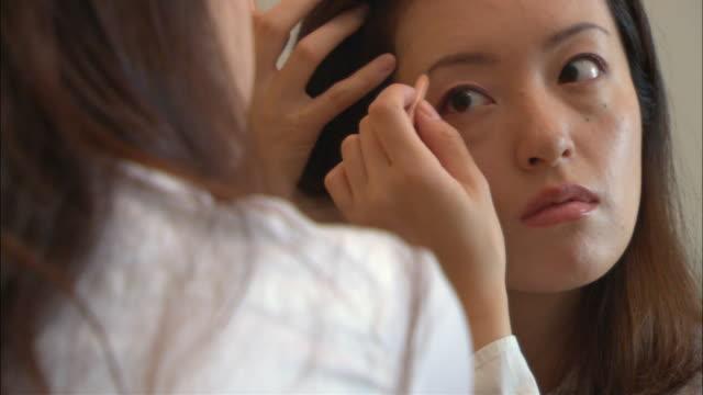 cu, woman applying make-up in front of mirror - 30代点の映像素材/bロール