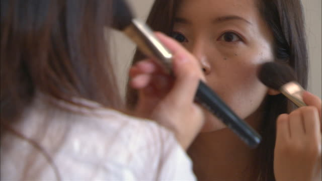 cu, woman applying make-up in front of mirror - メイクアップ点の映像素材/bロール
