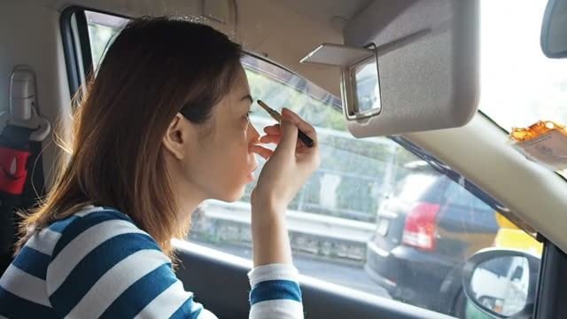 Woman applying makeup in the car