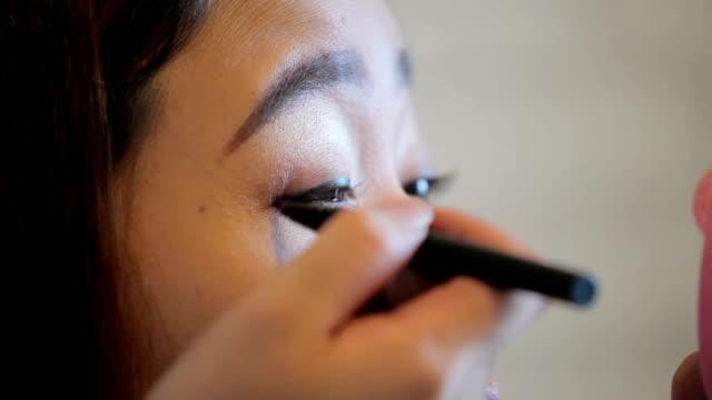 Woman applying makeup on her eyelash