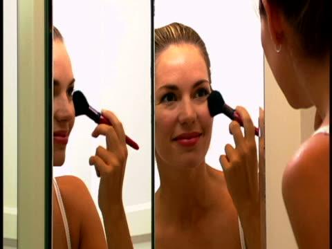 vidéos et rushes de woman applying make-up - pinceau à blush