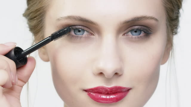 Woman applying mascara against white background