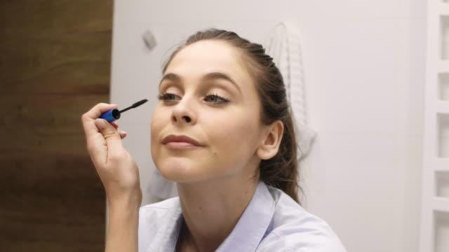 Woman applying mascara, Katowice, Poland