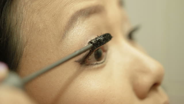 woman applying mascara on her eyelash