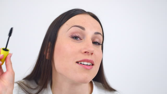 woman applying mascara to her eyelashes - mascara stock videos and b-roll footage