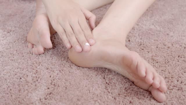 vídeos de stock, filmes e b-roll de mulher que aplica o creme do hidratante em seu pé. conceito do cuidado do corpo - moisturiser