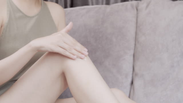 woman applying moisturizer cream on her leg.body care concept - inginocchiarsi video stock e b–roll