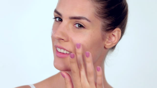 woman applying moisturizer onto face - rubbing stock videos and b-roll footage