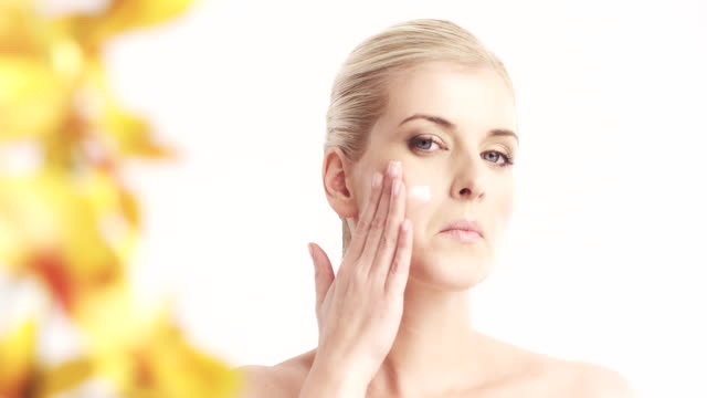 woman applying moisturizer to her face - sun cream stock videos and b-roll footage