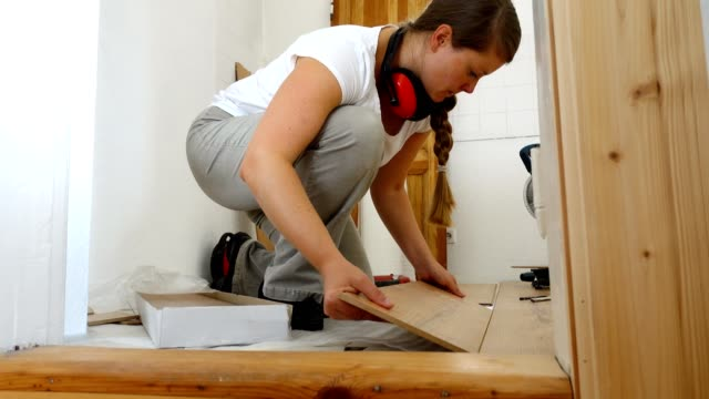 Woman applying new flooring.