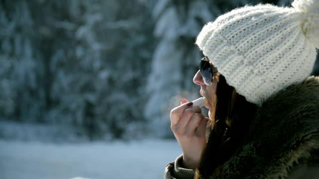 stockvideo's en b-roll-footage met vrouw toepassen van beschermende lippenbalsem - zichtbare adem