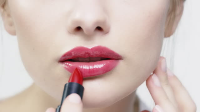 Woman applying red lipstick and blowing kiss