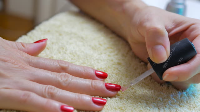 woman applying red nail polish after manicure treatment - red nail polish stock videos and b-roll footage